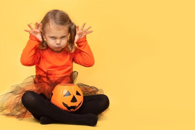 L'enfant tient le pot jack fait des grimaces le visage effrayant de la citrouille halloween un enfant en costume fait un visage terrible