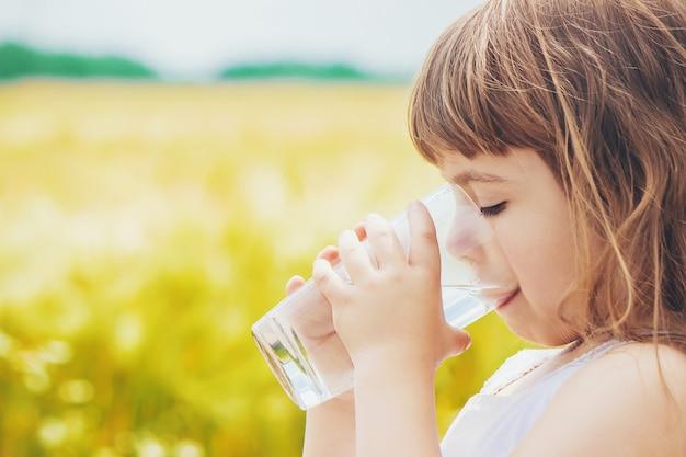 L'enfant tient un verre d'eau dans ses mains. mise au point sélective.