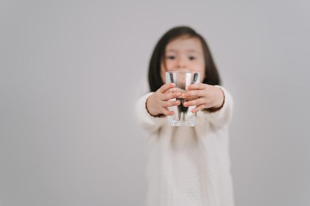 L'enfant tient un verre d'eau. la fille veut boire de l'eau.