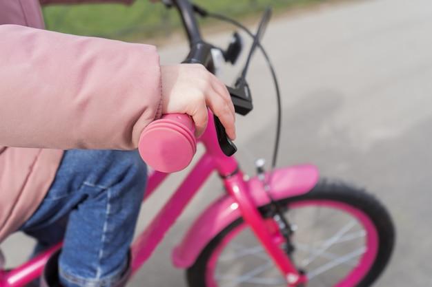 L'enfant tient le volant d'un vélo. une fille dans une veste rose fait du vélo.