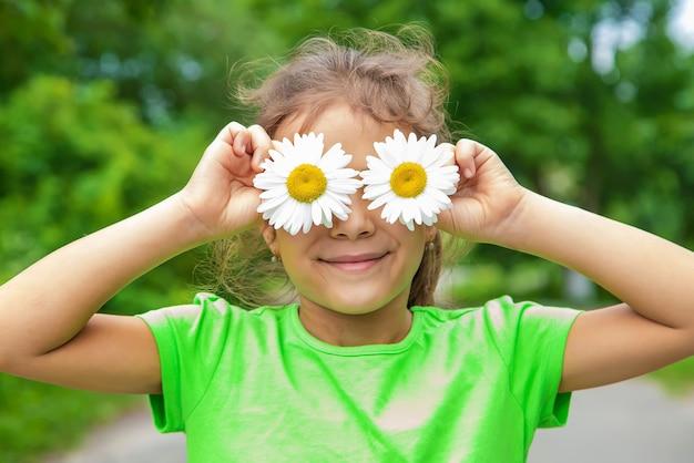 L'enfant tient des yeux de camomille sur son visage. mise au point sélective. nature.