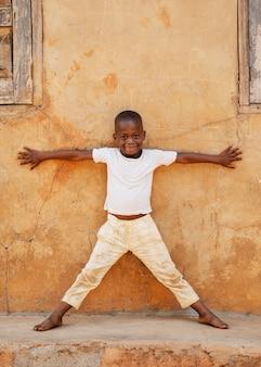 Enfant de tir complet posant près du mur