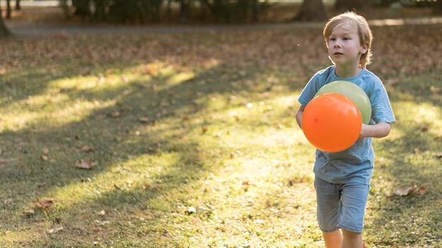 Enfant de tir moyen avec des ballons à l'extérieur