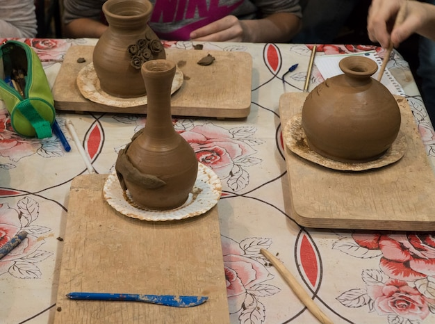 Enfant en train de décorer le pot en argile. atelier de poterie pour enfants