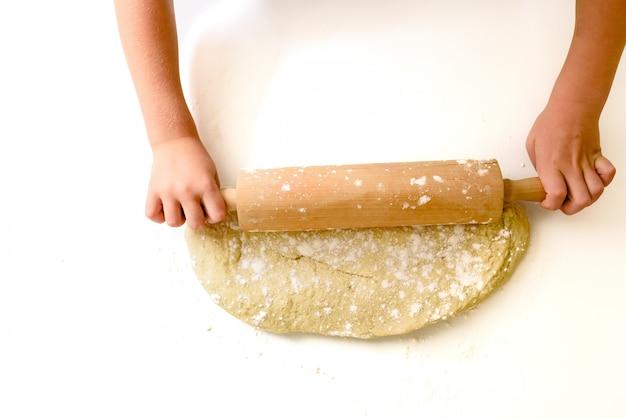 Enfant en train de pétrir la pâte d'une pizza, vue d'en haut.