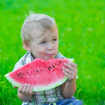 Enfant avec tranche de pastèque, manger à l'extérieur, pique-nique