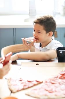 Enfant avec une tranche de pizza