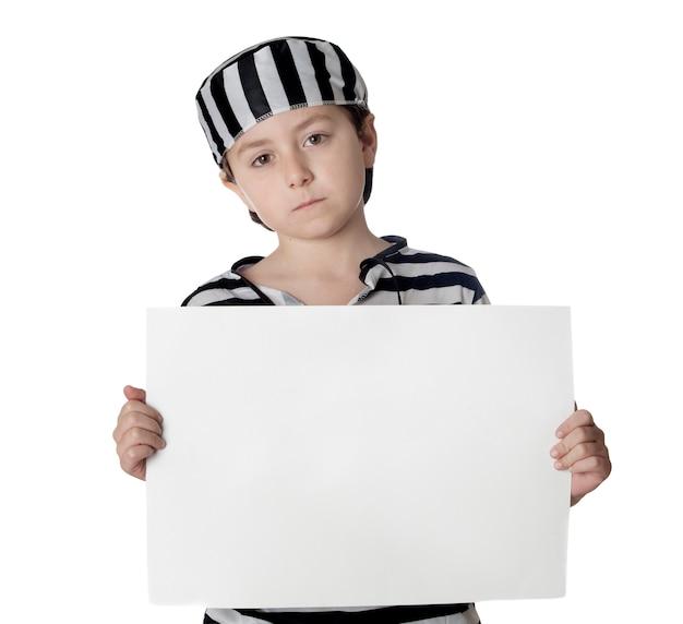 Enfant triste avec costume de prisonnier et affiche vide isolé sur fond blanc
