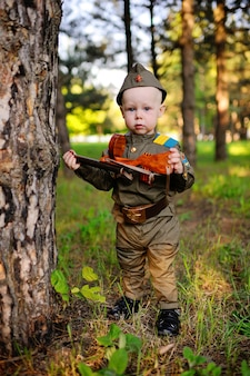 Enfant en uniforme militaire sur fond de nature