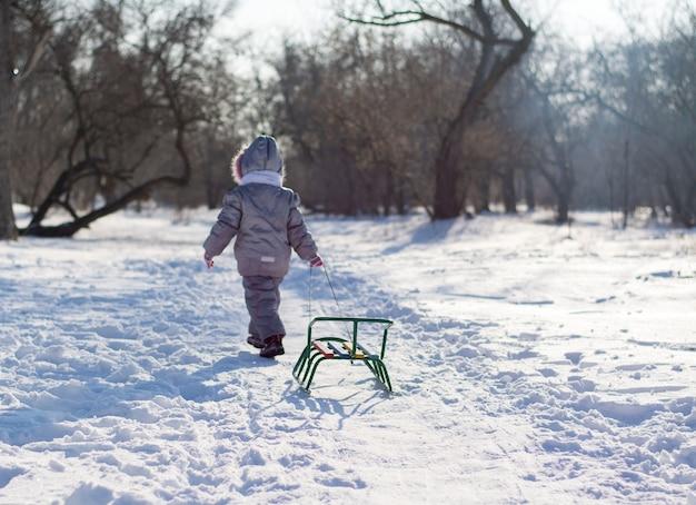 Un enfant va et traîne un traîneau à travers une clairière enneigée dans les bois