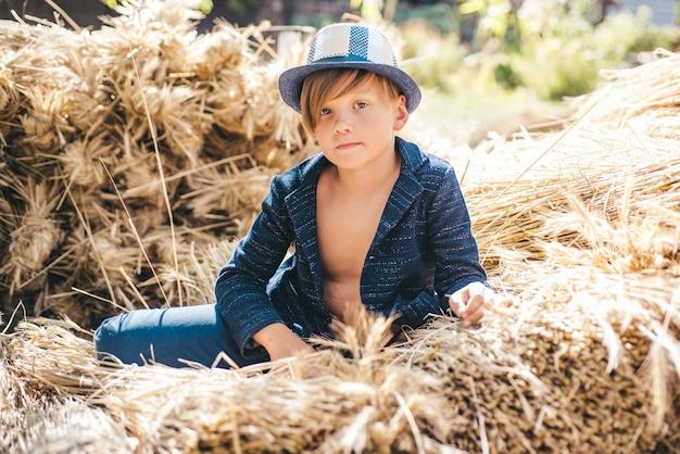 Enfant en vacances d'automne à la ferme. kid garçon tenant une feuille d'or et se trouve sur le foin