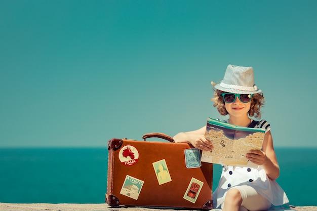 Enfant avec valise vintage et plan de la ville en vacances d'été concept de voyage et d'aventure
