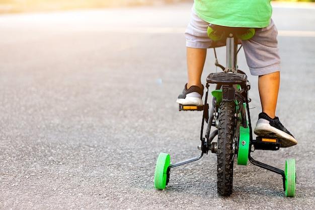Un enfant à vélo avec des roues de formation.
