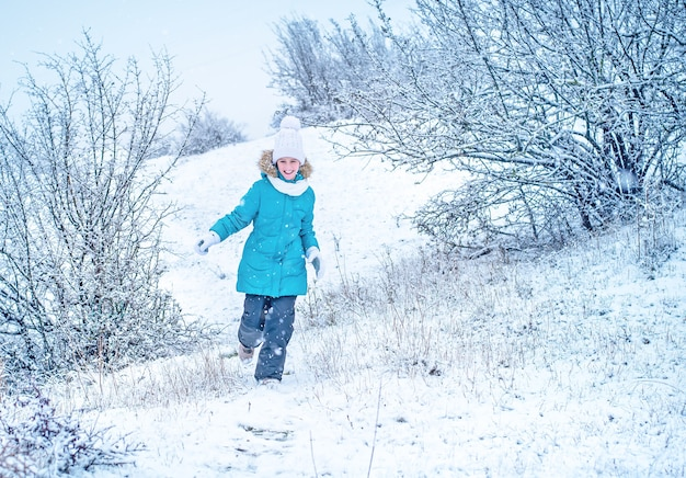 Un enfant en vêtements d'hiver court. fille dans la neige. plaisir d'hiver.