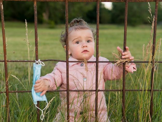 Enfant en vêtements roses derrière les barreaux du parc