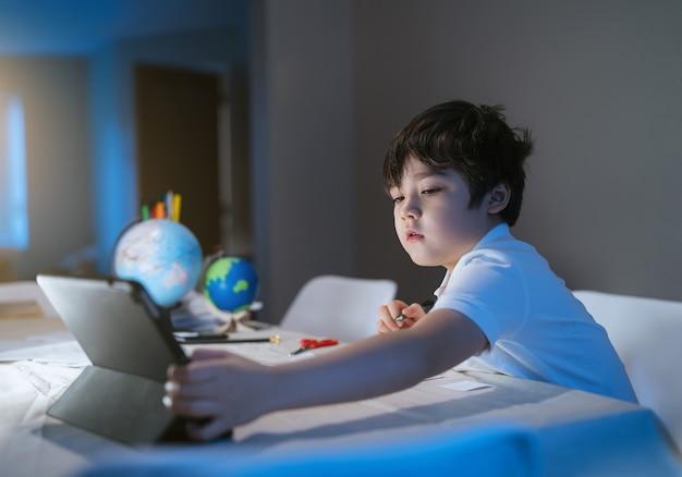 Enfant de la vie à l'aide de tablette pour ses devoirs à la maison