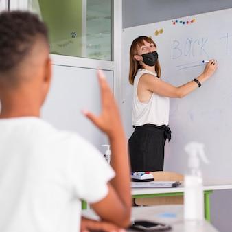 Enfant voulant poser une question pendant la classe