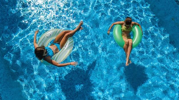 Les enfants actifs dans la piscine vue aérienne de dessus, les enfants heureux nagent sur des beignets gonflables et s'amusent dans l'eau en vacances en famille sur la station