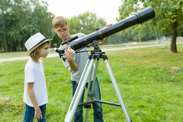 Enfants adolescents dans le parc regardant à travers un télescope