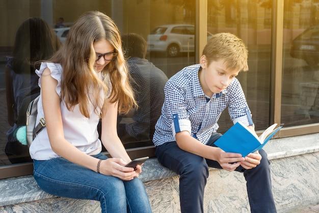 Enfants adolescents lire livre en utilisant smartphone,