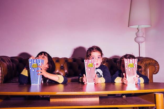 Enfants adorables avec pop-corn devant la télé