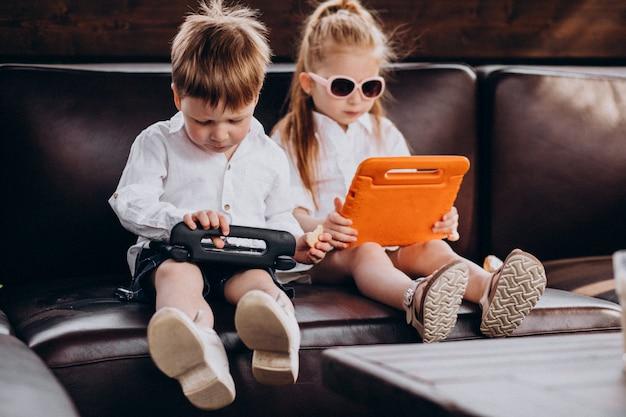 Enfants d'affaires assis sur un canapé à l'aide de tablettes