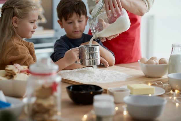 Des enfants affectueux cuisinant avec leur mère