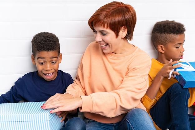 Enfants afro-américains avec leur mère parmi de nombreux cadeaux pour les vacances de noël