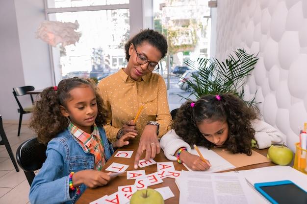 Enfants d'âge préscolaire bouclés. enfants d'âge préscolaire bouclés mignons se sentant attentifs tout en écoutant leur professeur de crèche pendant les cours