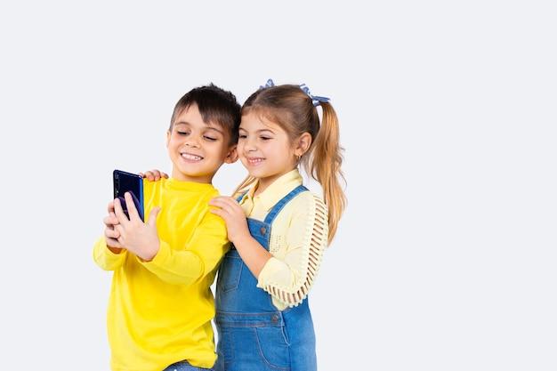 Enfants d'âge préscolaire heureux avec appel vidéo smartphone et souriant sur fond blanc.