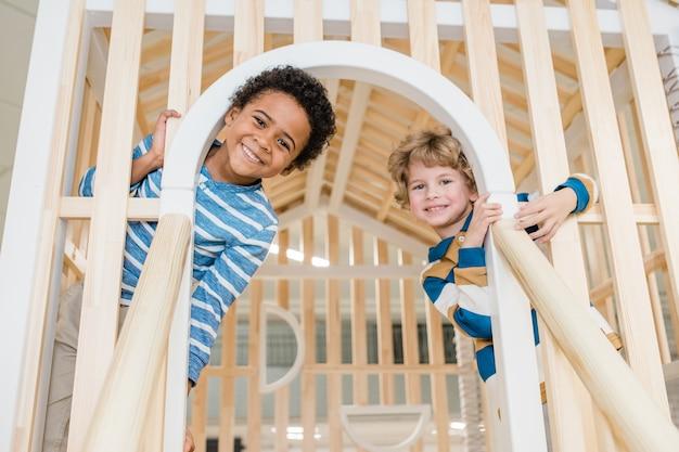 Enfants d'âge préscolaire joyeux mignons d'ethnies africaines et caucasiennes vous regardant tout en s'amusant sur l'aire de jeux