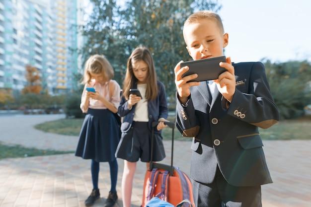 Enfants d'âge primaire avec smartphones