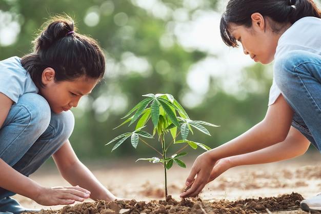 Enfants aidant à planter un arbre dans le jardin pour sauver le monde. concept d'environnement écologique