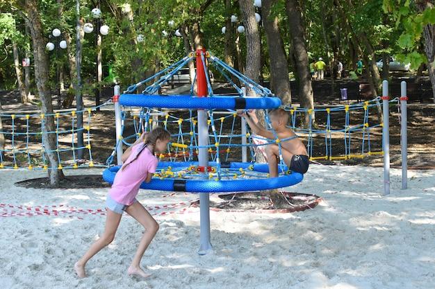Les enfants sur l'aire de jeux en été. drôles de vacances pour enfants en plein air. groupe sympathique d'enfants s'amusant
