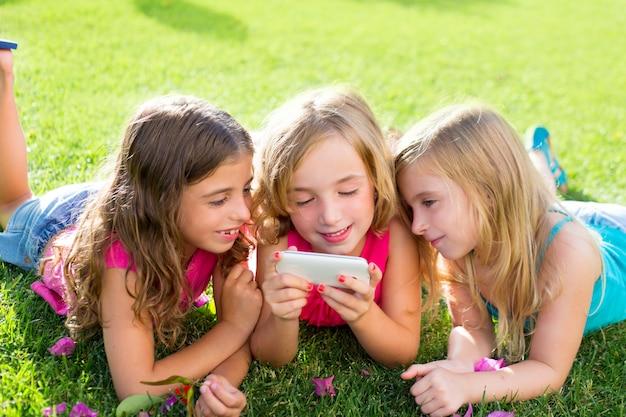 Enfants ami filles jouant à internet avec smartphone