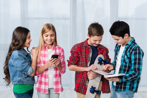 Enfants à angle élevé avec planche à roulettes et téléphone