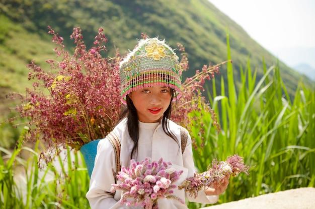 Enfants appartenant à une minorité ethnique non identifiés avec des paniers de fleurs de colza à hagiang, au vietnam. hagiang est une province la plus septentrionale du vietnam