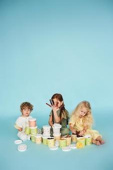 Les enfants apprécient différents types de pastilles sur fond bleu. concept d'alimentation saine pour les enfants.