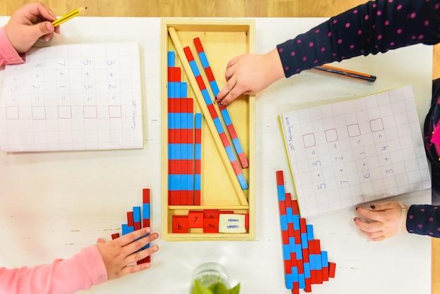 Enfants apprenant à écrire dans le domaine de l'alphabétisation dans une école montessori.