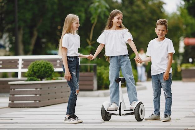 Les enfants apprennent à faire du hoverboard dans un parc aux beaux jours d'été