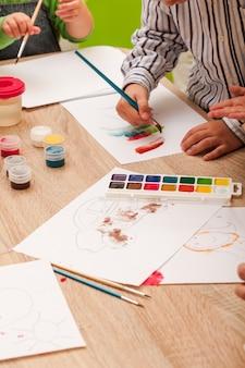 Les enfants apprennent à peindre avec un pinceau et des aquarelles sur papier à la maternelle
