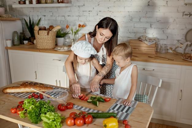 Les enfants apprennent à préparer une salade dans la cuisine. journée de congé en famille, déjeuner de vos propres mains. maman et jeunes cuisiniers