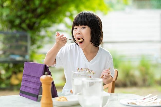 Les enfants asiatiques aiment manger de la nourriture