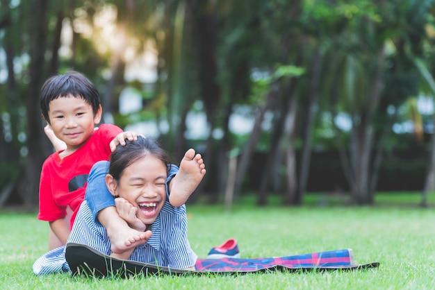 Enfants asiatiques allongez-vous et détendez-vous sur la pelouse verte du parc souriez en vous amusant et heureux