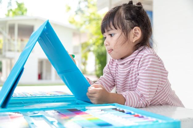Les enfants asiatiques apprennent à dessiner en classe.
