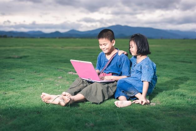 Des enfants asiatiques en costume local utilisent un ordinateur portable pour l'éducation et la communication dans la campagne thaïlandaise.