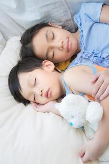 Enfants asiatiques dormant avec ours en peluche