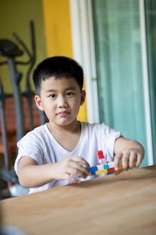 Enfants asiatiques jouant au jouet à la maison salon