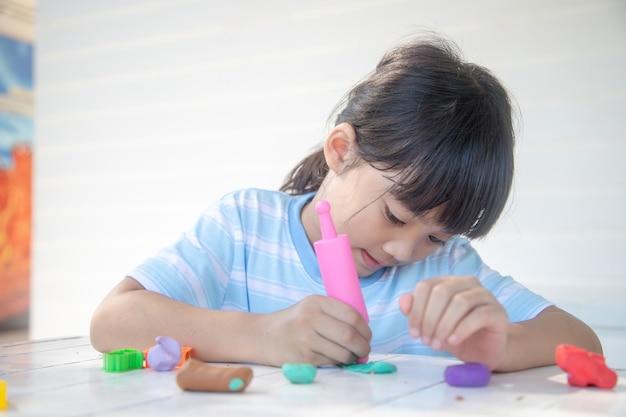 Les enfants asiatiques jouent avec des formes de moulage en argile, apprenant par le jeu