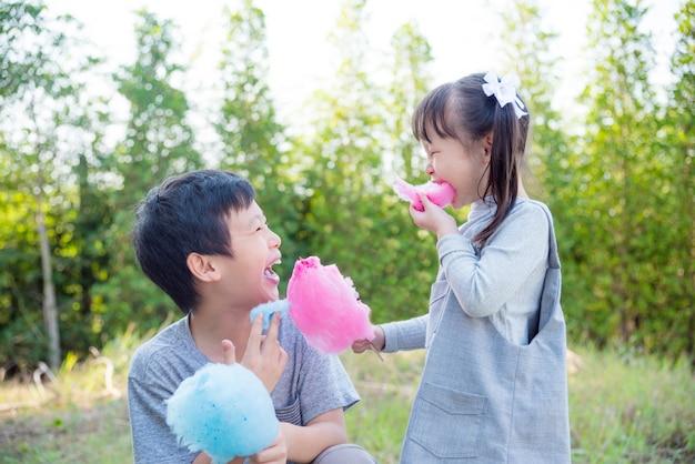 Enfants asiatiques mangeant une barbe à papa dans le parc ensemble